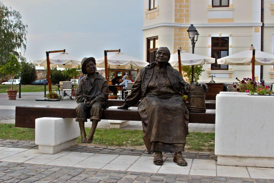 Bătrâna şi copilul care stau pe bancă în Piaţa Cetăţii îi îmbie pe turişti să ocupe loc lângă ei/Foto: Emanuel Drăguşin