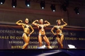 Clujeanca Bianca Mic (în centru),   căștigătoare a două medalii de aur la Campionatul Național de culturism și fitness din Bistrița