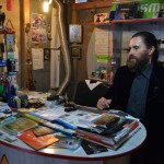 David Pleșa vinde și repară telefoane în service-ul său de pe strada Memorandumului,   într-o încăpere tapetată cu iconițe și calendare bisericești. (FOTO: Radu Hângănuț)