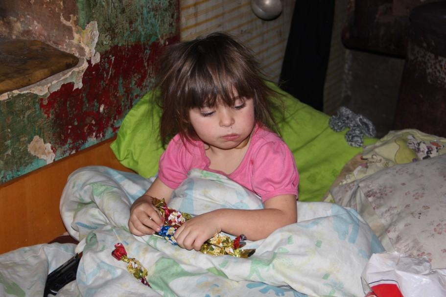 Sub plapumă și la orele amiezii pentru a nu îngheța de frig,   o fetiță de cinci ani și-a luat în primire dulciurile/Foto: Dan Bodea