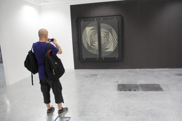"""Iosif Király,   în fața unei lucrări din expoziția """"1.1.1. + Sigma1 Expoziție retrospectivă: Poetica spațiului.Utopie și cercetare""""/Foto: Dan Bodea"""