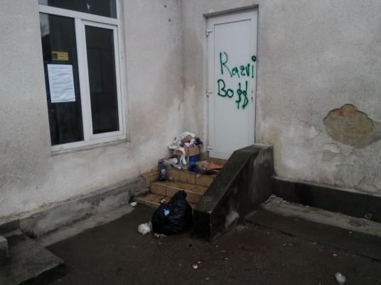 Alături de ușa în spatele căreia se află alimentele de la UE zace o grămadă de gunoi