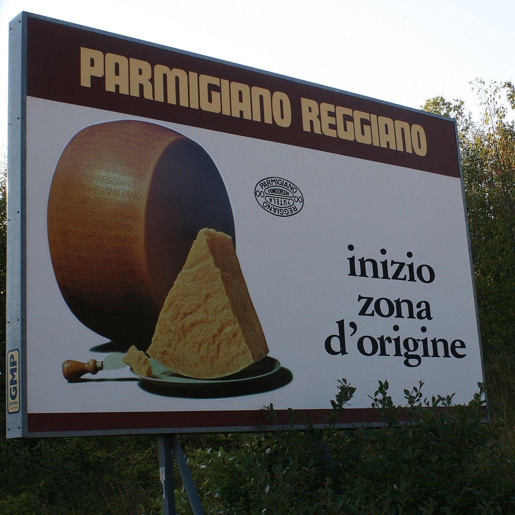 Panou în Italia,   care indică faptul că intri într-o regiune de origine a adevăratului Parmigiano-Reggiano.