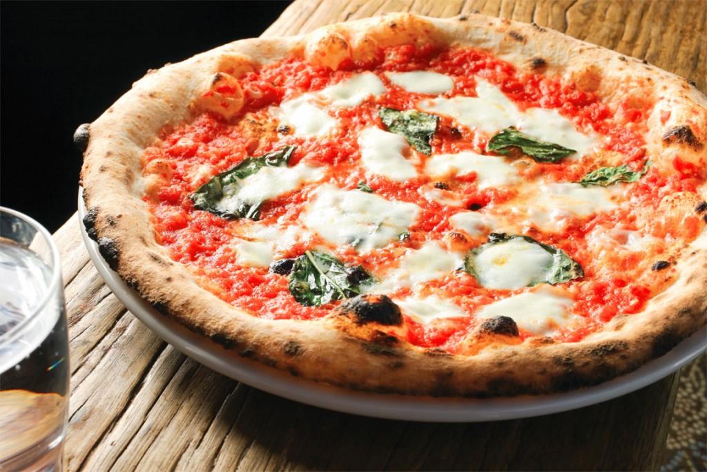 """Legenda spune că """"adevărata"""" pizza a fost inventata în Napoli,   la începutul secolului 18. Varianta Margherita,   care se găseşte peste tot,   a apărut în 1889 şi a fost denumită după regina Margherita de Savoia. Ingredientele sale principale reflectau culorile drapelului italian: roşii,   mozzarella albă şi frunze de busuioc verzi."""
