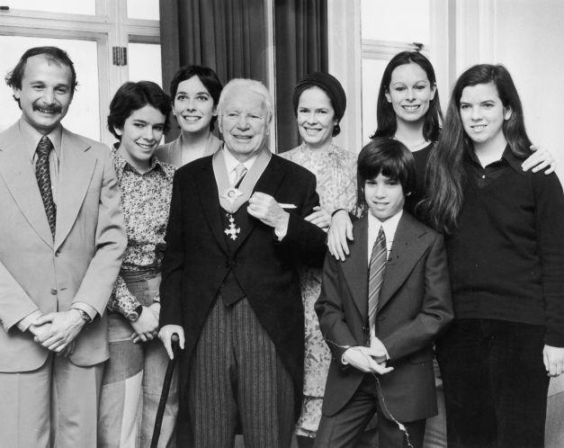 Charlie Chaplin la bătrânețe,   alături de soția lui,   Oona (în centru,   în spatele lui) și de șase din cei opt copii ai lor.