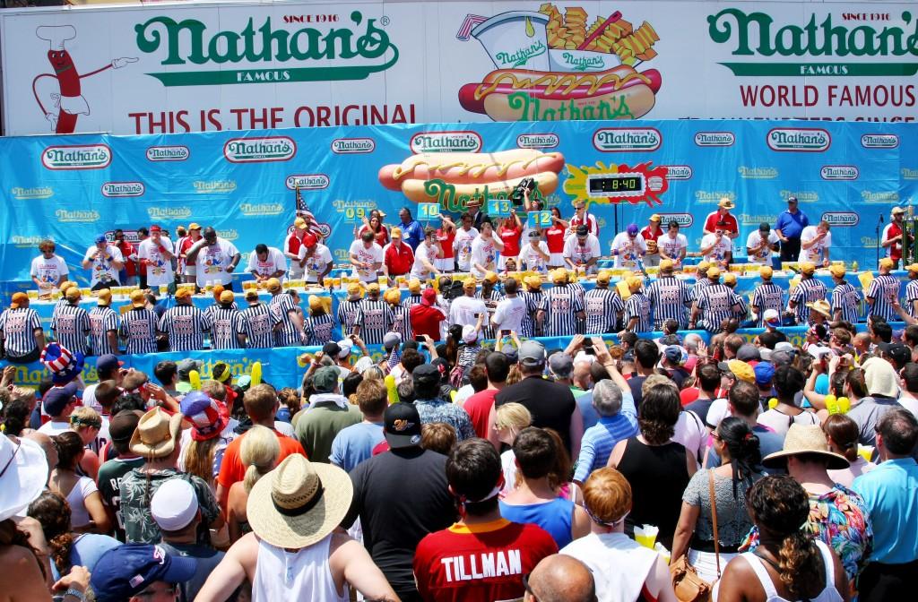 Cel mai aşteptat concurs de mâncat hot dogs este cel organizat de Nathan's Famous - un lanţ de restaurante dezvoltat dintr-un stand mobil deţinut de un imigrant polonez,   Nathan Handwerker. Acesta a început să vândă hot dogs în Coney Island,   în 1916,   după ce a luat un împrumut de 300 de dolari de la nişte prieteni. Astăzi,   Nathan's sunt celebre pentru cârnăciorii lor – iar restaurantul iniţial încă există în Coney Island.