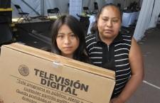 Susana Lopez de 11 ani alături de mama sa,   fericită că a primit un televizor pe care familia nu-și permitea să-l cumpere. Foto: Tim Johnson/McClatchy DC/TNS