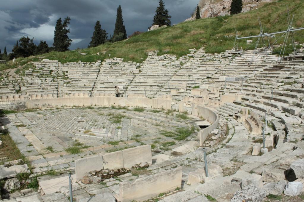"""Tot din secolul 5 î.e.n., datează şi cel mai important edificiu destinat reprezentaţiilor teatrale – """"Teatrul lui Dionysos"""", din Atena, construit sub Acropole şi transformat, ulterior, în amfiteatru cu bănci de piatră în semicerc."""