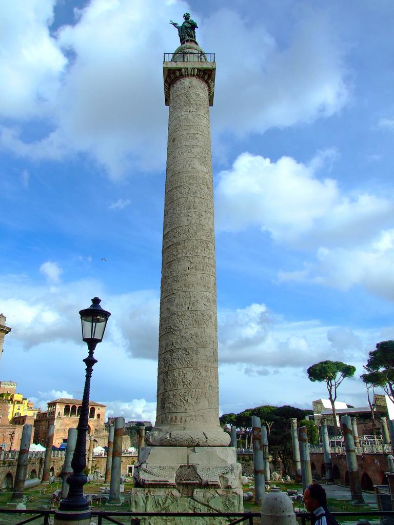 Iniţial,   în vârful Columnei se afla o statuie a unui vultur,   dar după moartea împăratului Traian,   aceasta a fost înlocuită cu o statuie înaltă de peste 6 metri care îl înfăţişa pe Traian.  Cenuşa lui Traian şi apoi a soţiei acestuia,   Plotina,   au fost depuse la baza coloanei.