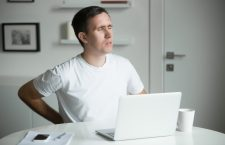 Young man with his hands at his back, stretching near the white desk after working at laptop, the mug, mobile aside, home interior. Back pain pose. Business concept photo, lifestyle